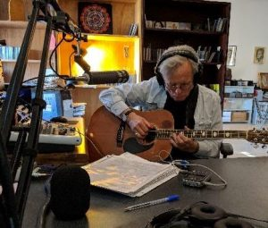 A man is playing the guitar. On the table in front of him is a microphone and headphones.