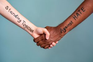 "two hands, one black, one white,  clasped in friendship. Written on their arms is the phrase ""Standing together against hate"""