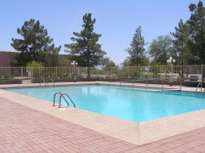 a large, welcoming swimming pool with a ladder and a wheelchair ramp for access.